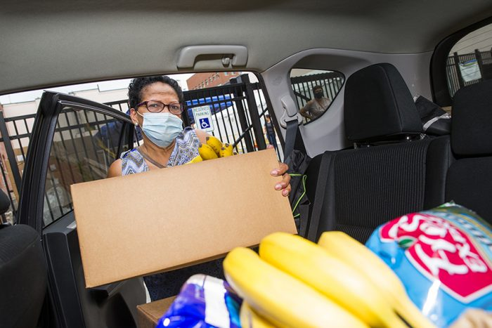 woman in mask loads box of food into car