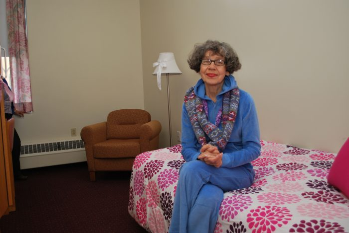 elderly woman sits on bed