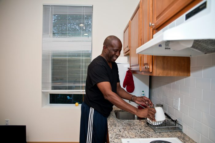 man washes dishes while smiling