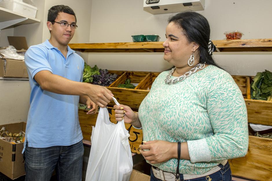 man handing woman a bag of groceries