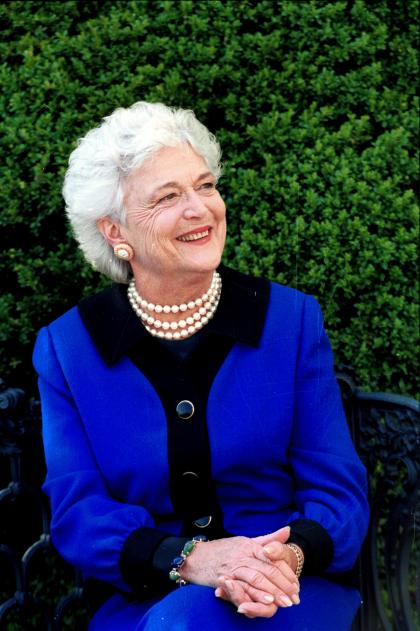 Barbara Bush smiling on a bench