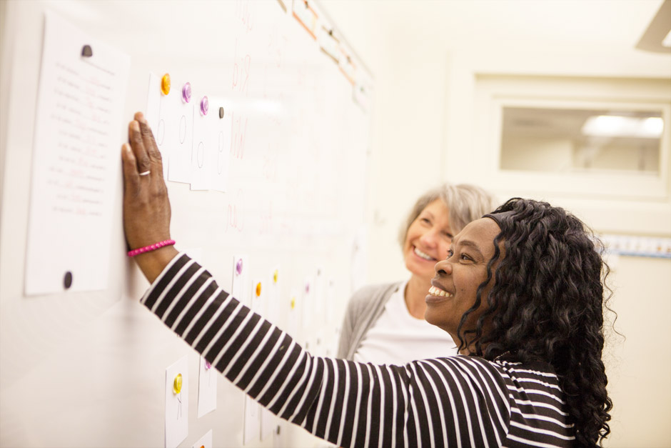 two woman smiling at whiteboard