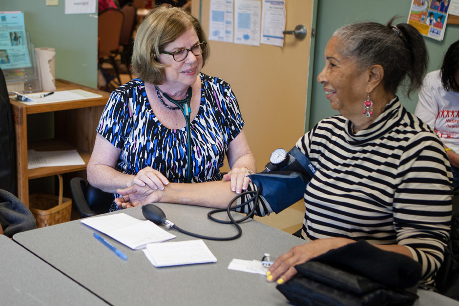 woman taking another woman's blood pressure