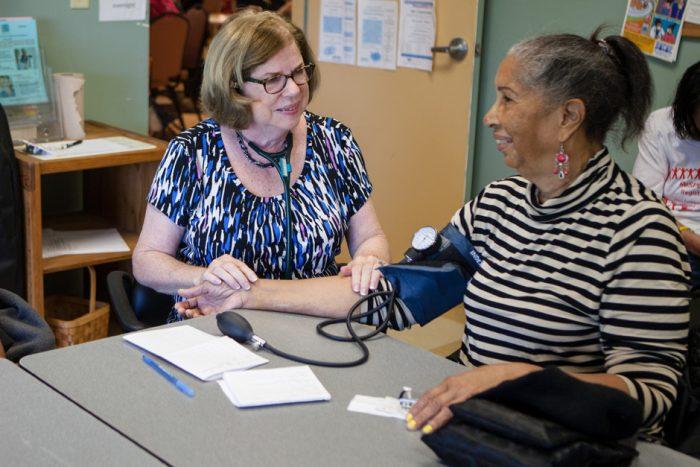 woman taking a woman's blood pressure